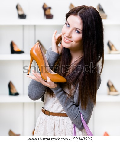 Half-length portrait of woman keeping brown leather stylish shoe in shopping center - stock photo