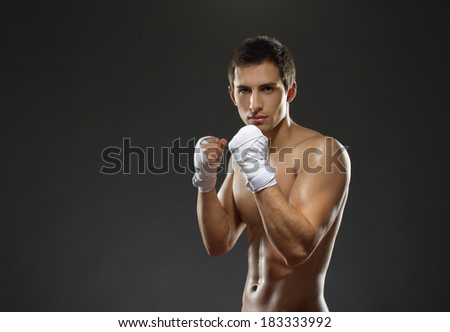 Half-length portrait of working out fighter with hands wrapped with elastic bandage, isolated on black - stock photo