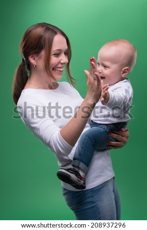 Half length portrait of young attractive Caucasian mother and cute baby smiling and giving high five, isolated on green - stock photo