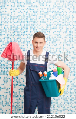 Half-length portrait of young dark-haired smiling janitor wearing white T-shirt blue overalls and yellow rubber gloves holding red mop in one hand and blue pail with cleaners in another