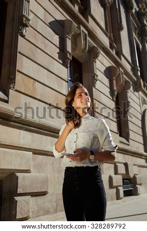 Half length portrait of young dreaming female strolling in urban setting in spring sunny day, attractive woman using mobile phone for navigation in the city, stylish hipster girl using technology - stock photo