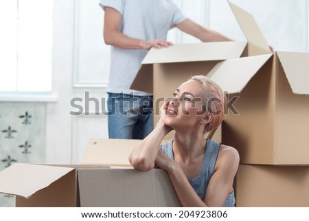 Half-length portrait of young fair-haired girl sitting among the boxes and because of her removal and waiting for her guy - stock photo
