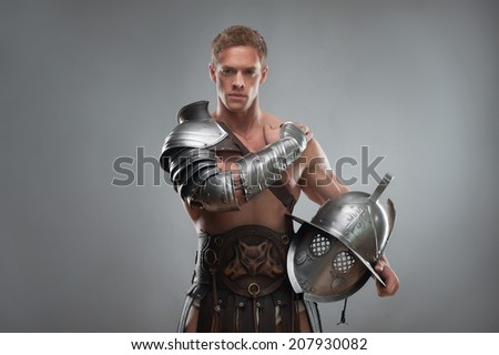 Half length portrait of young handsome muscular man gladiator in armour posing with helmet isolated over grey background - stock photo