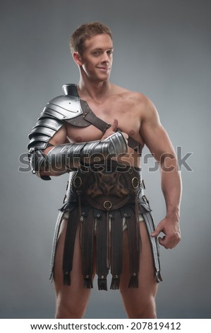 Half length portrait of young handsome muscular man gladiator in armour showing his thumb up isolated over grey background, concept of success, victory - stock photo