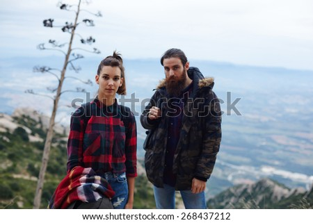 Half length portrait of young hikers resting after long way standing on mountain trail with beautiful view on background - stock photo