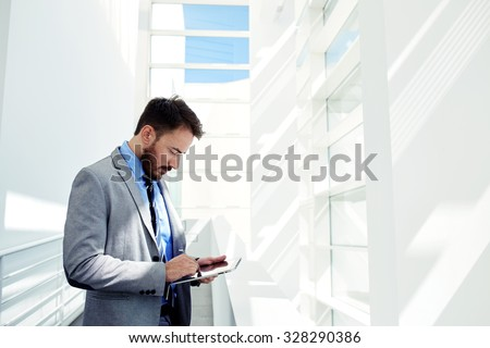 Half length portrait of young male managing director using touch pad in modern office interior with copy space area, skilled business man dressed in elegant corporate clothes work on digital tablet - stock photo