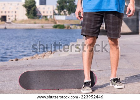 Half-length portrait of young man wearing shorts blue and trainers standing near his skateboard on the quay - stock photo