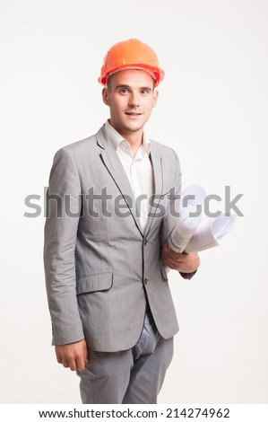 Half-length portrait of young smiling handsome architect engineer in orange helmet posing with blueprints looking at camera - stock photo