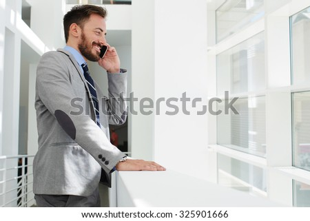 Half length portrait of young smiling smart businessman talking on smart phone while standing in hallway of his company, cheerful intelligent male ceo dressed in luxury suit speaking on cell telephone - stock photo