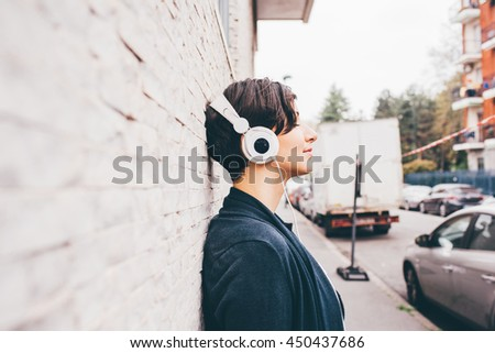 Half length profile portrait of young handsome caucasian brown hair woman leaning against a wall, listening music with headphones, eyes closed - serene, enjoying, music concept - stock photo