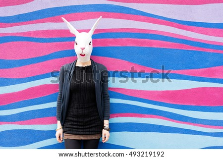 Half length woman wearing rabbit mask outdoor in the city leaning against colorful wall - halloween, dreamlike, strange concept