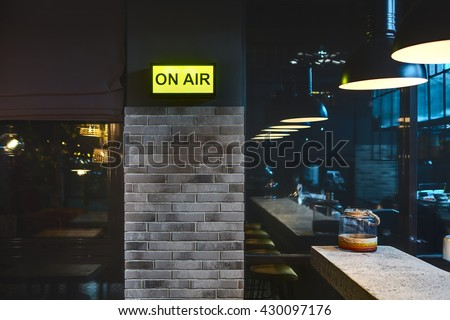 Half-lighted room in a mexican restaurant. There is a brick wall with glowing signboard and windows. On the right there is a light rack with jar on it and glowing lamps over it. Other side of the room - stock photo