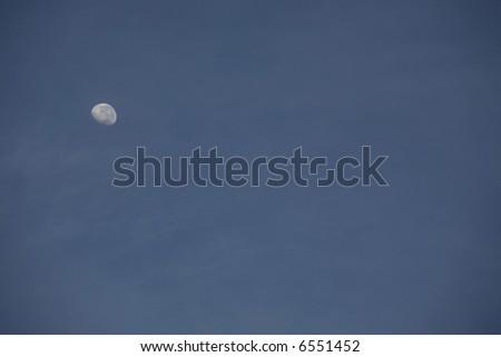 Half moon against a blue sky. - stock photo