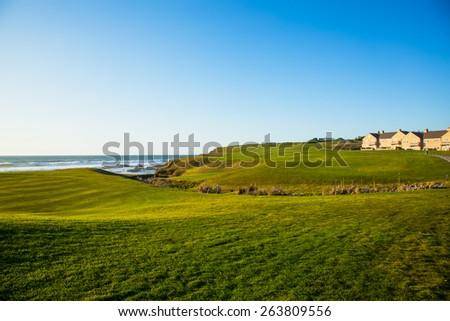 Half Moon Bay grass field and villa houses.  Golf course. - stock photo