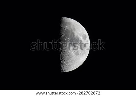 Half moon during the first quarter phase isolated against a black sky. - stock photo
