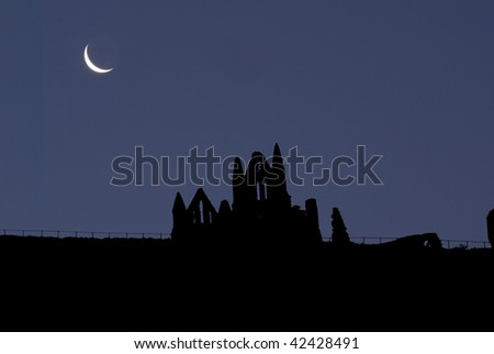 Half-moon over Whitby Abbey and St Mary's Church in silhouette - stock photo