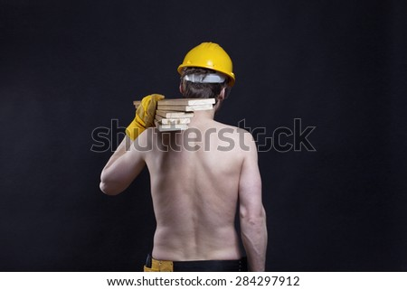 Half naked carpenter carrying wooden planks on his shoulder, back side view - stock photo