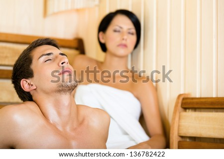 Half-naked man and girl relaxing in sauna. Concept of self-care, health and relaxation - stock photo