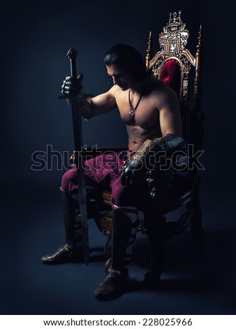 Half-naked man on a throne with a sword in his hand sits deep in thought - stock photo