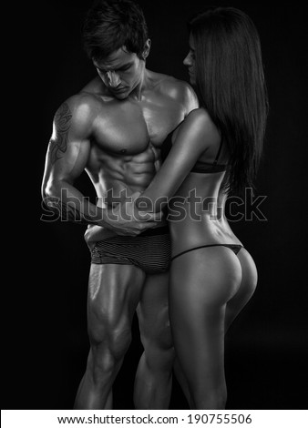 half-naked sexy couple, muscular man holding a beautiful woman isolated on a black background - stock photo
