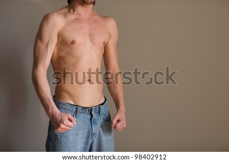 Half-naked young man against the wall - stock photo