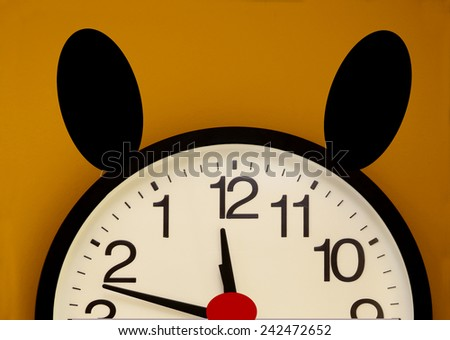 Half of a wall clock with red nose, black ears and the order of the numbers inverted - stock photo