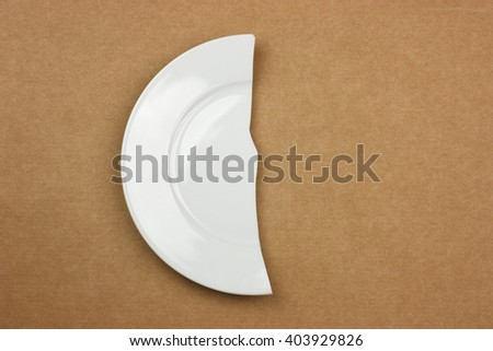 Half of broken plate on cardboard background - diet concept