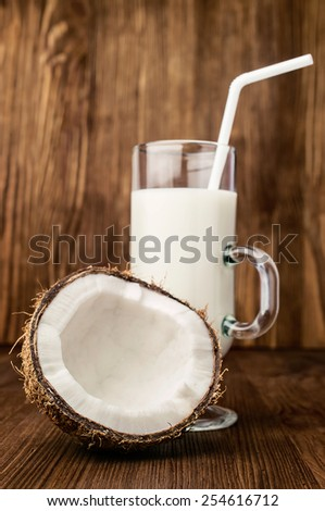 half of fresh coconut and coconut milk in a glass on wooden - stock photo