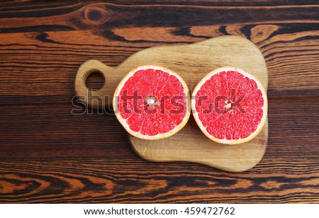 half of grapefruit on a wooden board on a wooden table
