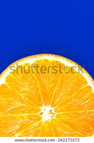 Half of juicy fresh orange isolated on blue background - stock photo