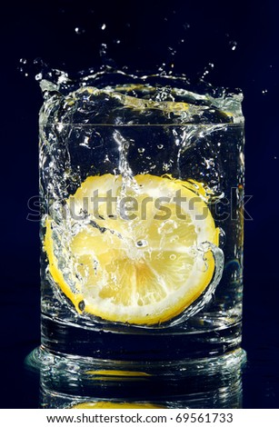 Half of lemon falling down in glass with water on deep blue - stock photo