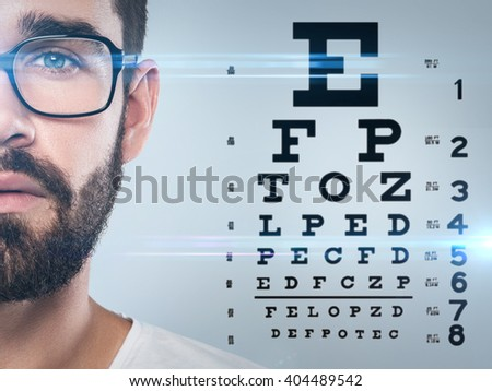 Half of male face and eye chart on background - stock photo