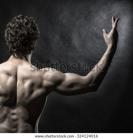 Half of one handsome sexy strong muscular young man with bare back and curly hair standing with raised hands indoor in studio on black background, square picture - stock photo