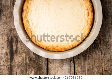 Half of pie on wood background. Fresh baked cheesecake on wooden table. Menu and recipe image. - stock photo