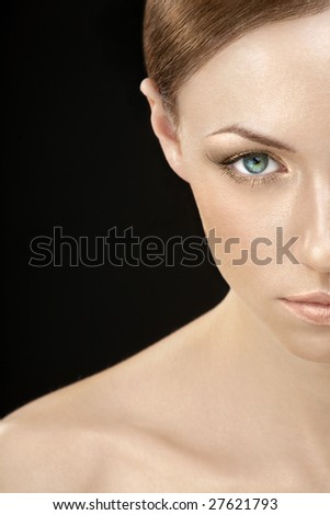 Half of the face of the woman with a golden make-up on a black background - stock photo