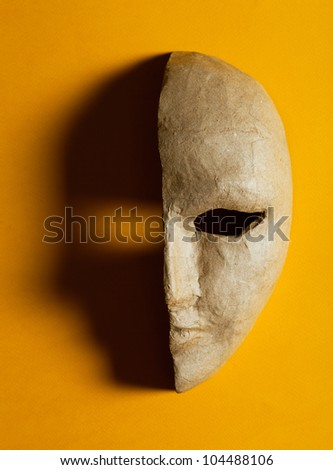 half of the paper masks on a yellow background - stock photo