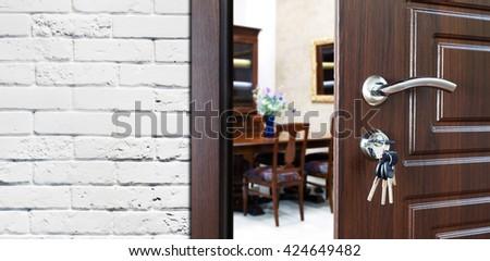 Half opened door to a cabinet or office. Door handle, door lock. Lounge door half open. Opening door. Privacy, welcome concept. Entrance to the room. Door at white brick wall, modern interior design. - stock photo