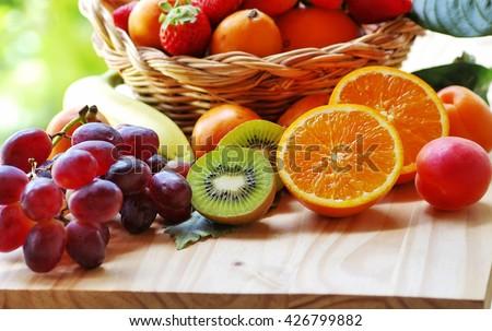 half orange, sliced kiwi, other fruits in the basket - stock photo