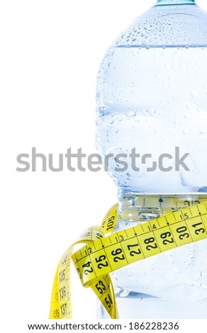 half plastic bottle with water, drops and measuring tape on white background, concept of nutrition and diet with space for text - stock photo