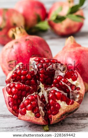 Half pomegranate and raw pomegranates on a white wooden background - stock photo
