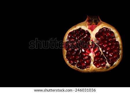 Half pomegranate on the right side isolated on black - stock photo