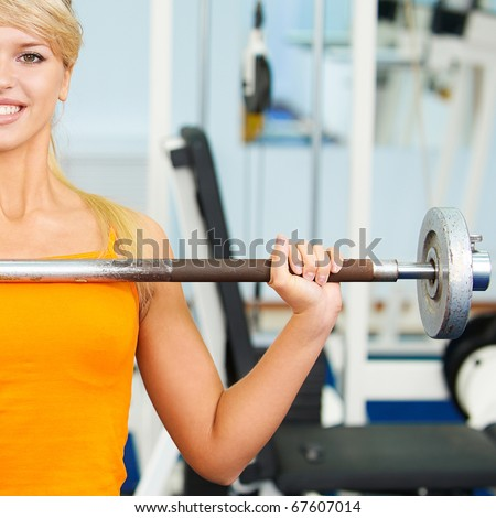 half portrait of blonde girl exercising in gym with weight