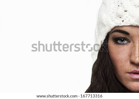 Half portrait of brunette young woman in white warm hat. Isolated on white background. - stock photo