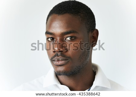 Half profile shot of attractive young African man with moustache and beard in casual clothes, looking at the camera with serious confident expression, posing against white concrete wall background - stock photo