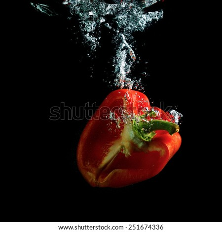 Half red pepper falling in water with air bubbles. Photo on black background. - stock photo