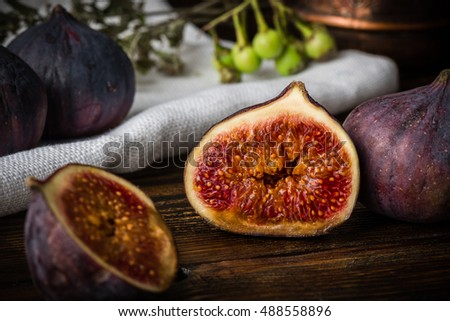 Half ripe and juicy fig lying on rustic table. Seasonal and exotic fruit