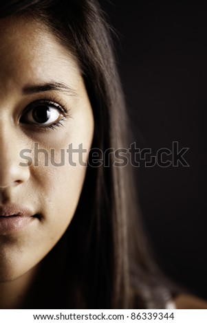 Half the face of a cute pretty teenage female girl isolated against a black background