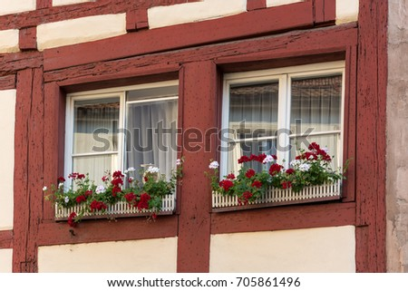 Half-timbered house with window shutters and colorful flowers