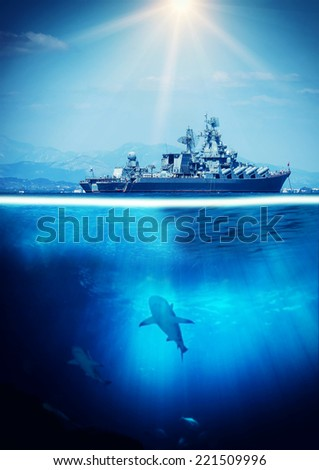 Half under and above water with war ship and sharks - stock photo
