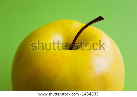 Half yellow apple on a green background - stock photo